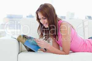 Teenager reading a review while lying on the couch