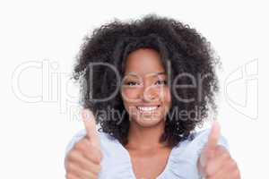 Young woman putting her two thumbs up in satisfaction