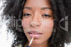 Young woman using a lip gloss applicator to make-up