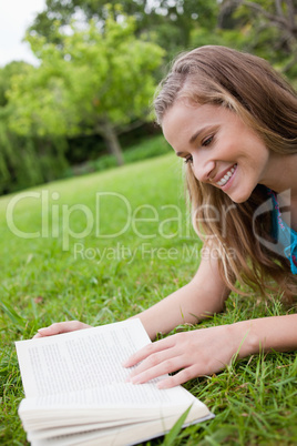 Young smiling woman reading a book while lying in a parkland