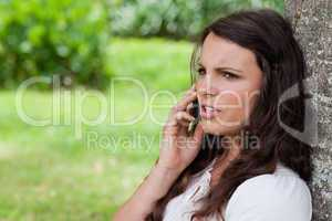 Young serious woman looking away while calling with her cellphon