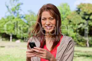 Young woman smiling happily while holding a phone