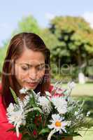 Young woman looking down at a flowers while standing in a park