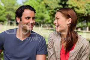 Man is grinning while he watches his friend who is laughing
