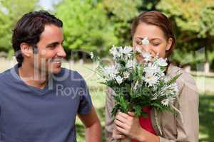 Man smiling as he watches his friend smell a bunch of flowers