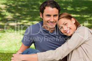 Man smiling as his friend rests his rests her head on his should