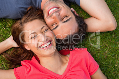 Two friends smiling while lying head to shoulder with an arm beh