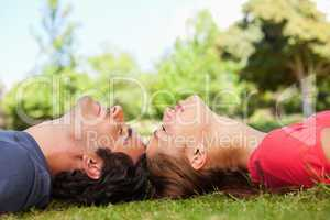 Two friends with their eyes closed while lying head to head