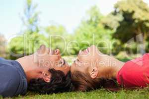 Two smiling friends with their eyes closed while lying head to h
