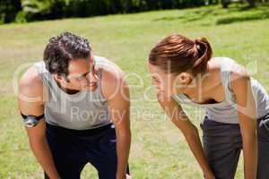 Man and a woman bending over while looking at each other
