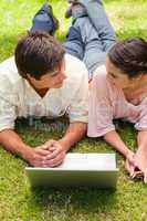 Two friends looking at each other as they lie down with a laptop