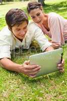 Two friends smiling as they watch something on a tablet together