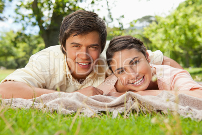 Two friends lying together on a blanket while smiling