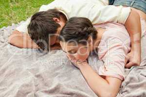 Man with his arm around his friend while lying on a blanket