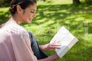 Woman reading a book while sitting in the grass