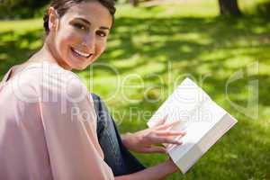 Woman looks to her side while reading a book in the grass