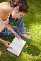 Woman looks down at a book while sitting on grass