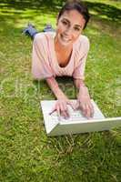 Woman looking ahead while using a laptop as she lies down in gra