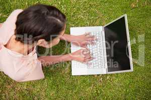 Elevated view of a woman using a laptop while lying down