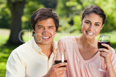 Two friends looking ahead while holding glasses of wine
