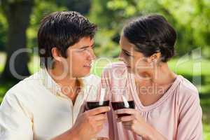 Two friends looking at each other while touching glasses of wine