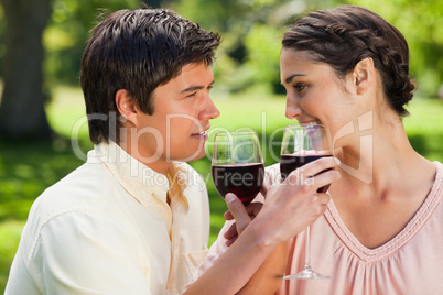 Two friends linking their arms while holding glasses of wine