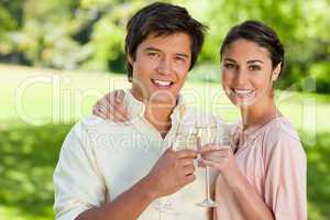 Two friends smiling while touching glasses of champagne