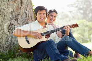 Man playing the guitar while ahead with his friend