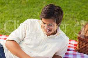 Man smiling as he lie on a picnic blanket