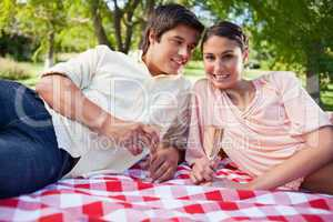 Man looking at his friend while as they lie down on a blanket wh