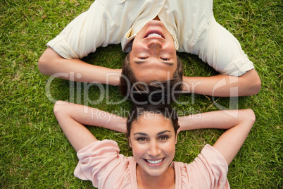 Two friends smiling while lying head to head with both hands beh