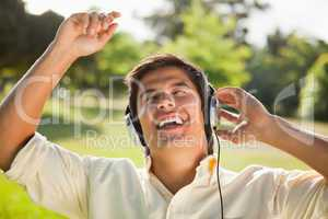 Man raising his arms while using headphones to sing along to mus