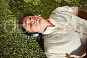 Man with his eyes closed while using headphones to listen to mus