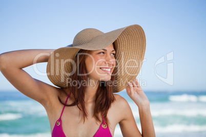 Smiling teenager standing in front of the sea while looking on t