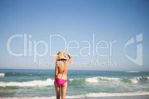 Back view of a young woman in beachwear standing in front of the