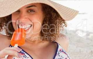 Young woman looking at the camera while eating a delicious ice c