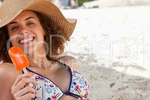 Smiling woman showing a beaming smile while holding an ice looly