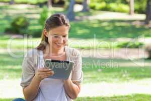 Smiling woman with her tablet computer sitting on the lawn