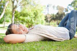 Woman lying on the grass while listening to music