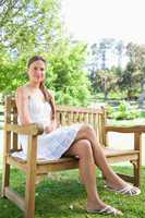 Woman with her legs crossed sitting on a park bench