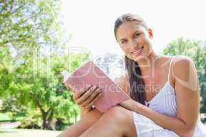 Side view of a smiling woman with a novel in the park