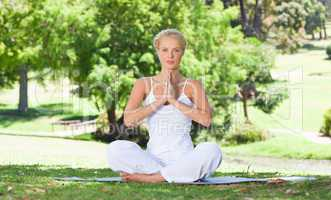 Woman on the grass doing yoga exercises