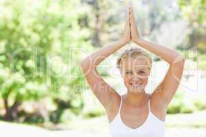 Relaxed smiling woman doing yoga in the park
