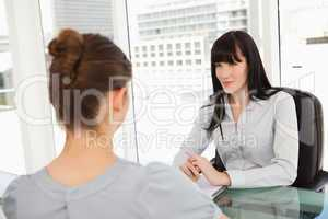 A smiling business woman listens to what the other woman has to