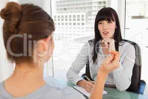 A business woman listens to the other woman in her office