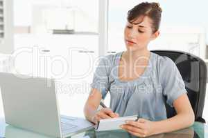 A woman takes notes off of her laptop