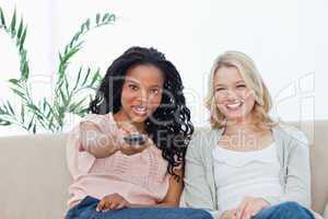 A woman with her friend is pointing a television remote control