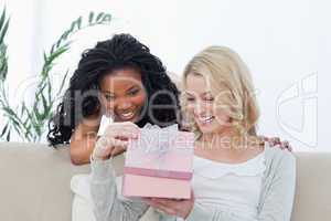 Two women look inside a pink box