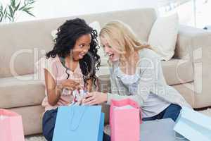 Two women looking at clothes in shopping bags