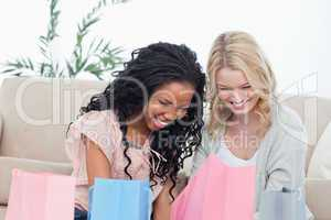 Two smiling women sitting on the floor with shopping bags